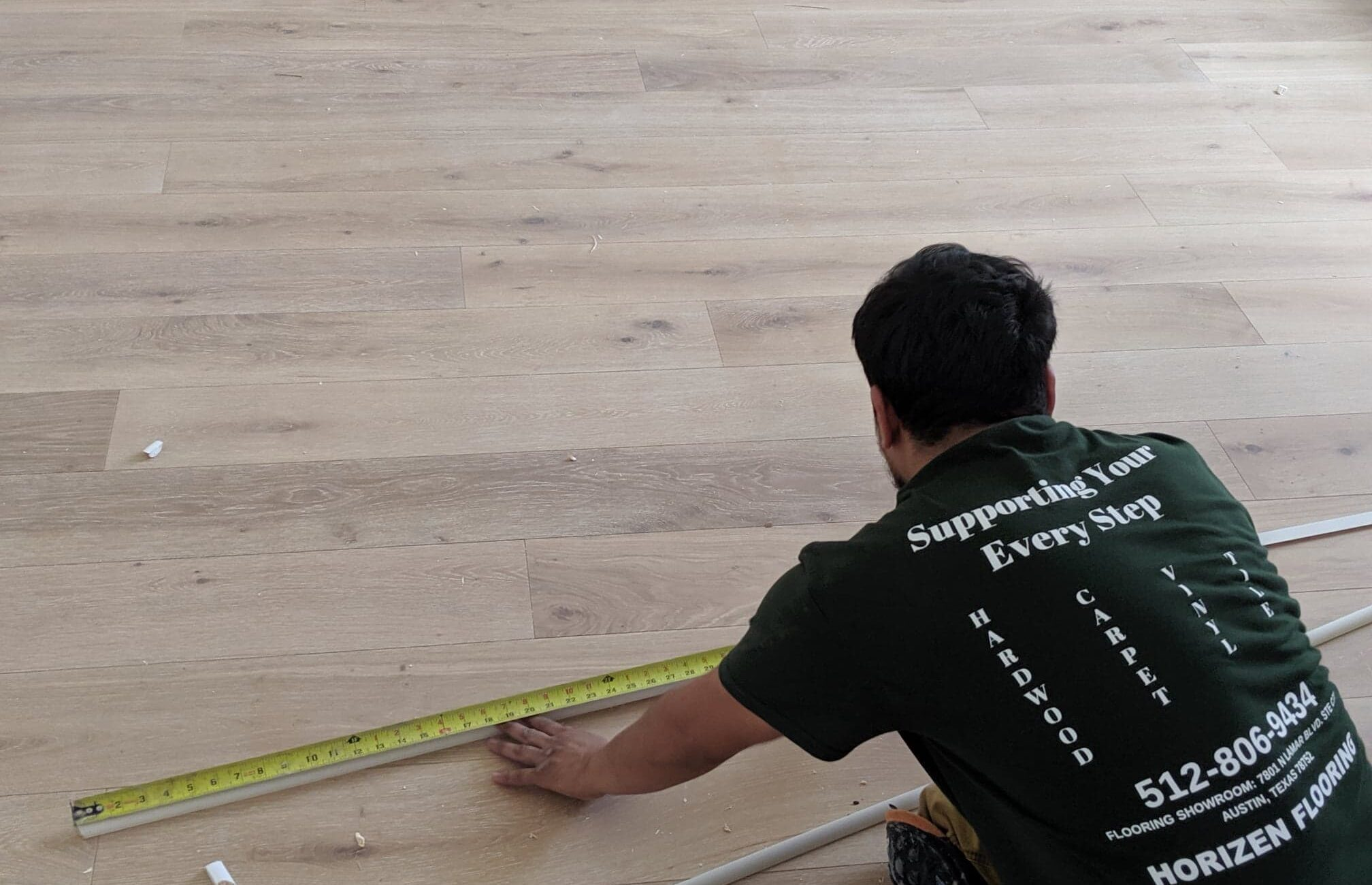 Horizen Flooring craftsman diligently working on the finishing touches to an engineered hardwood flooring installation